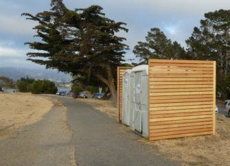 Lipstick on a pig: Wooden lattice installed around back and sides of plastic porta-potties